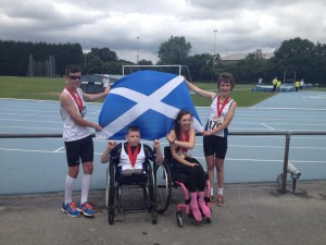 Four Scottish Para athletes celebrate medals with a Saltire flag
