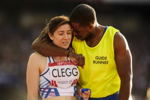 Guide runner Mikail Huggins puts arm around Libby Clegg after Hampden gold