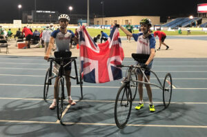 Gavin Drysdale with teammate Rafi Solaiman. They're on a floodlit blue track, astride their RaceRunners, holding a GB flag between them